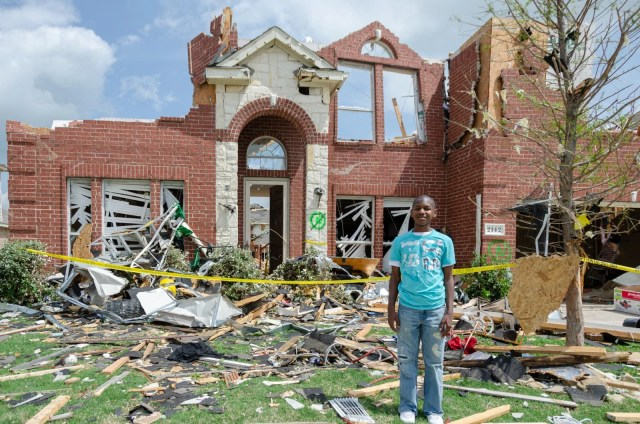 A kid standing in front of his home destroyed by a tornado
