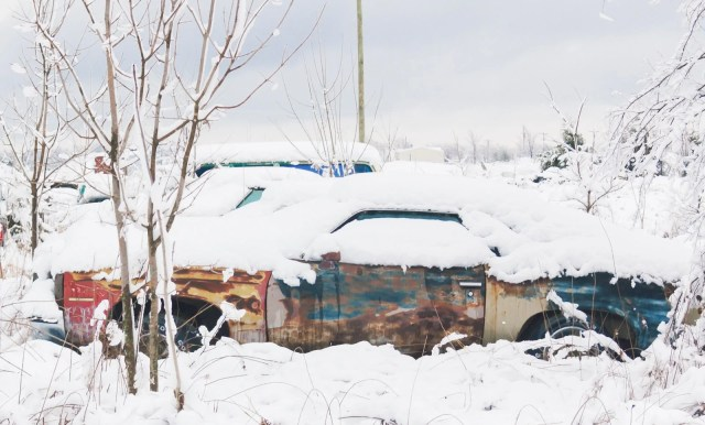 An abandoned rusted car in the snow