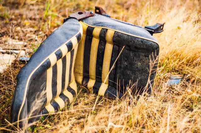 A black and yellow seat at an abandoned junkyard
