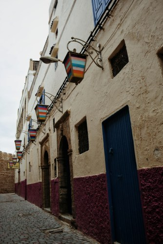 an alley next to the fortress wall lined with colorful lanterns