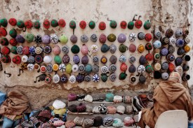 a hat-seller displays dozens of hats for sale