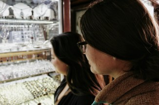 two young women look into a display case of rings and necklaces