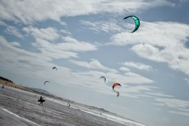 several kites in the sky and a man going with one to the ocean