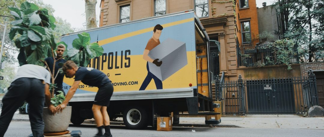woman in blue shorts and black boots standing beside yellow and white truck during daytime