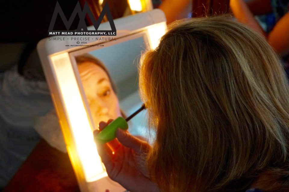 woman applying mascara in a lighted mirror before family portrait photo session in Ligonier, PA