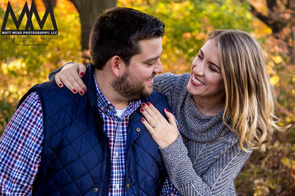 Engaged couple smiling in the fall in Pittsburgh, PA