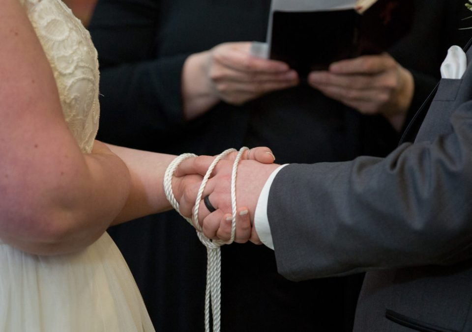 handfasting ceremony during vows at winter wedding in Erie, PA