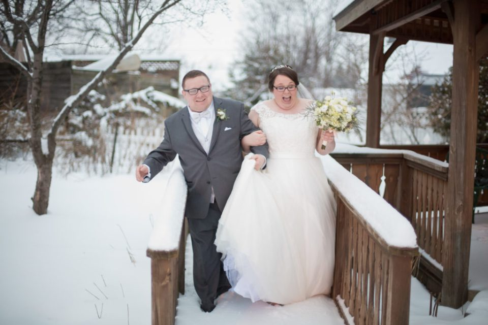 bride and groom slding through snow at winter wedding in Erie, PA