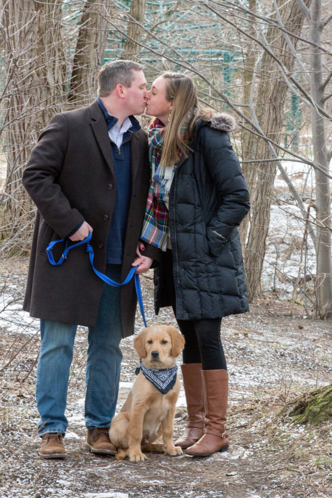 couple kissing while walking their Golden Retriever puppy at Frontier Park in Erie, PA