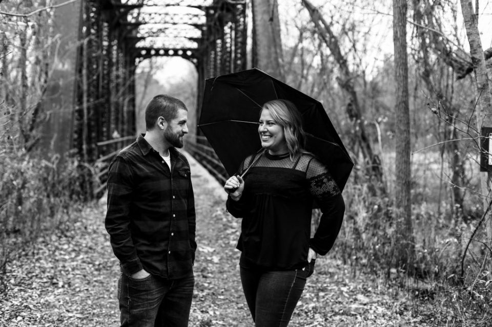 Erie, PA engaged couple standing at the entrance to railroad bridge holding an umbrella