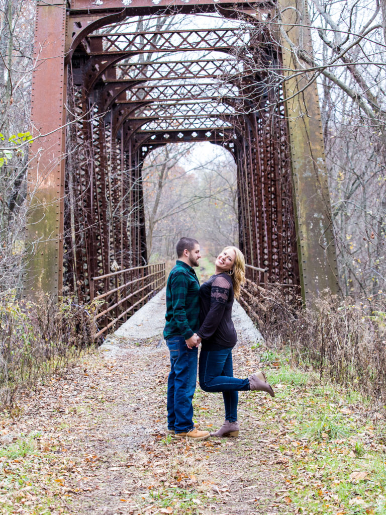 engaged couple standing at entrance to railroad bridge in Erie, PA