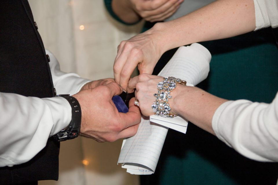 close up shot of bride and groom exchanging rings in Erie, PA