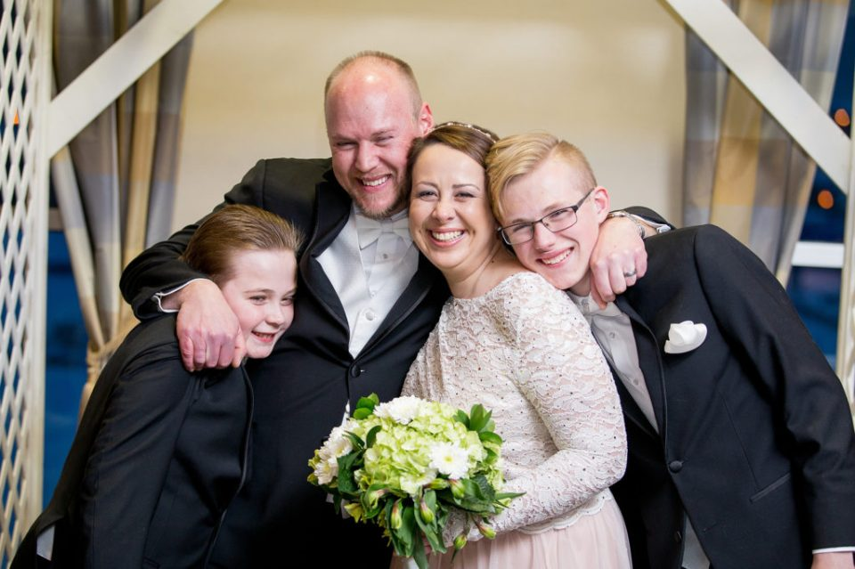 Bride, groom and groom's sons pose together at Sheraton Bayfront hotel wedding in Erie, PA