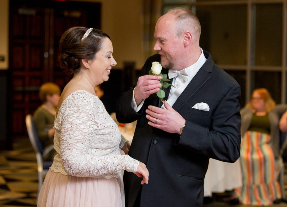groom pulls white rose from pocket at Sheraton Bayfront hotel wedding in Erie, PA