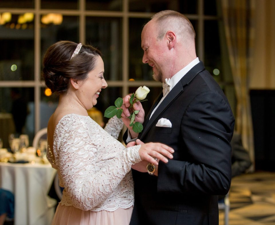 groom hands white rose to bride during first dance at Sheraton Bayfront hotel wedding in Erie, PA