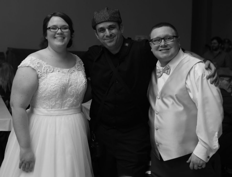 bride and groom pose with photographer, Matt Mead, at their winter wedding in Erie, PA
