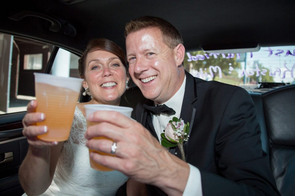 bride and groom toasting in limo in Erie, PA