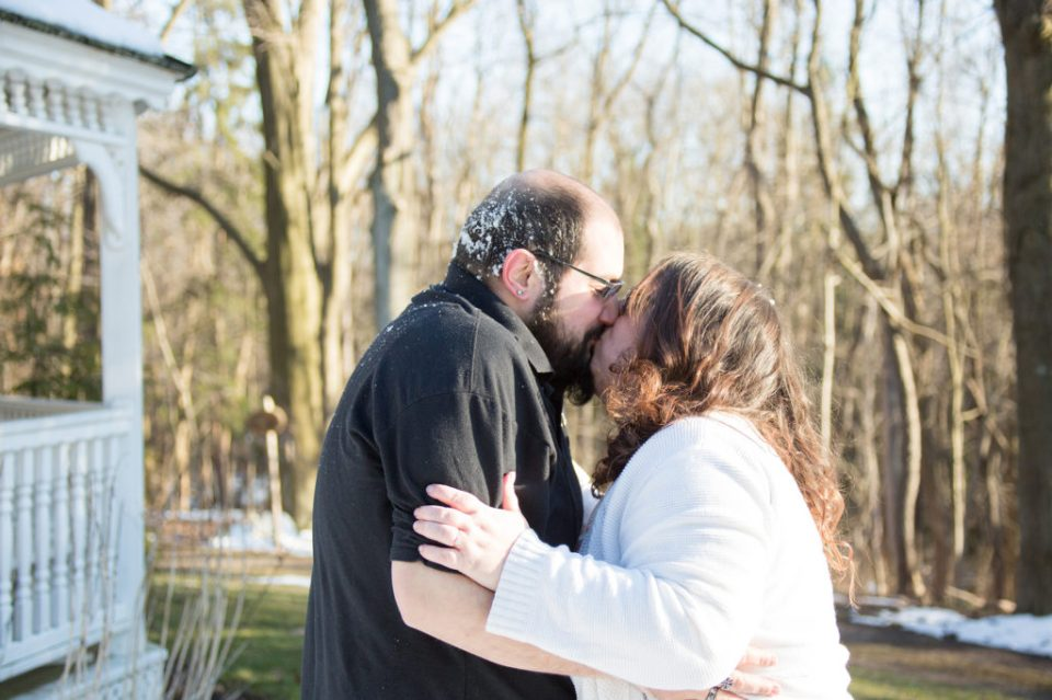 snow covered couple share a kiss during a Robin Hill Park engagement session near Pittsburgh, PA