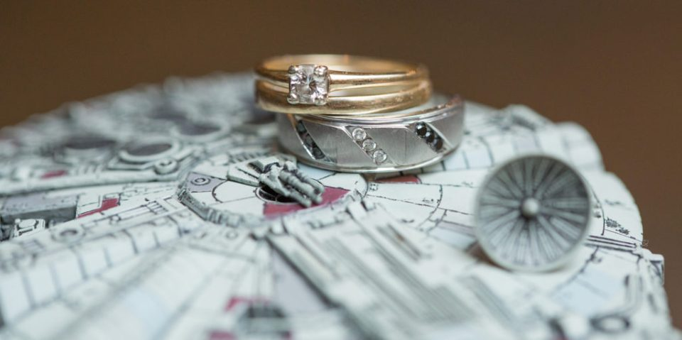 wedding rings resting on Millenium Falcon cake topper at Star Wars themed wedding