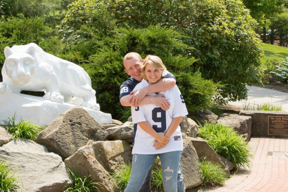 couple pose next to Nittany Lion statue at Penn State Erie campus
