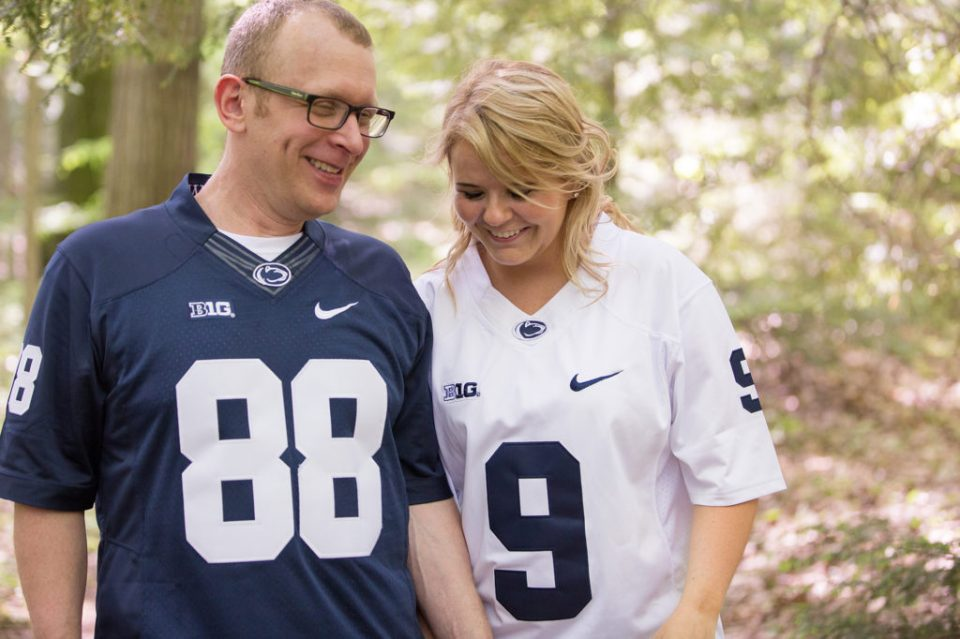 Couple wearing Penn State football jerseys walk through arboretum at Penn State Behrend in Erie, PA