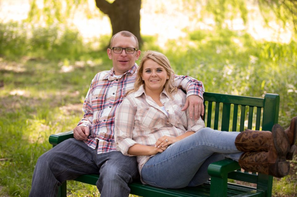 Engaged couple sitting on a bench in Frontier Park in Erie PA