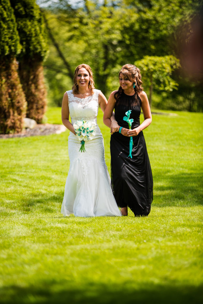 Maid of honor escorts bride down the aisle in Erie PA backyard wedding