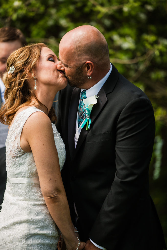bride and groom share first kiss in Erie PA backyard wedding