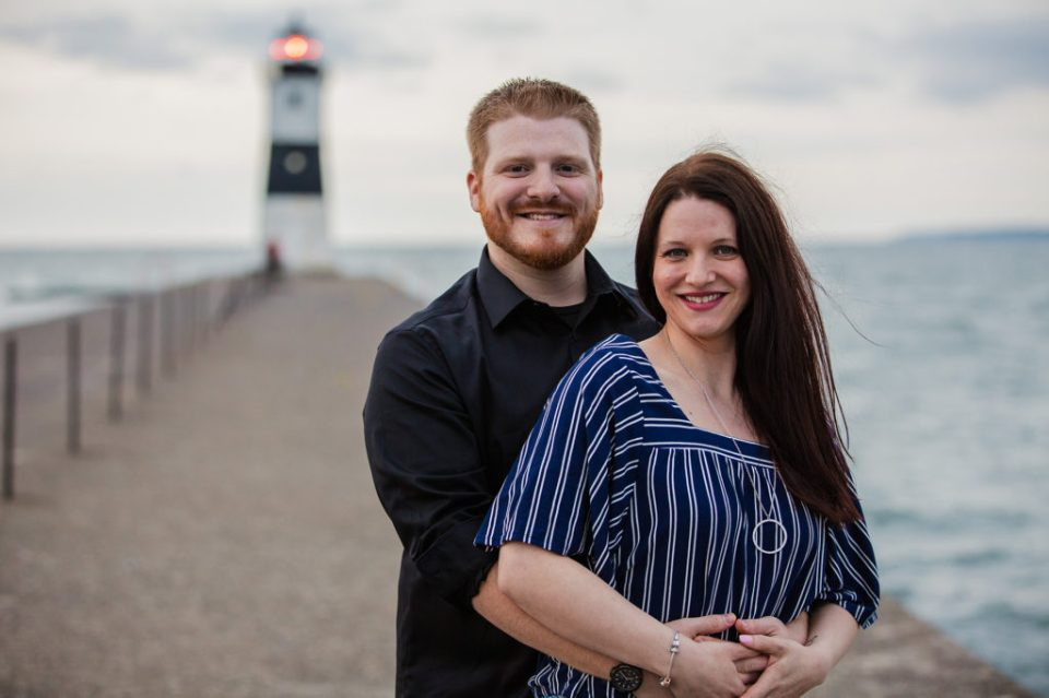 engaged couple smiles for engagement portrait at North Pier in Erie, PA