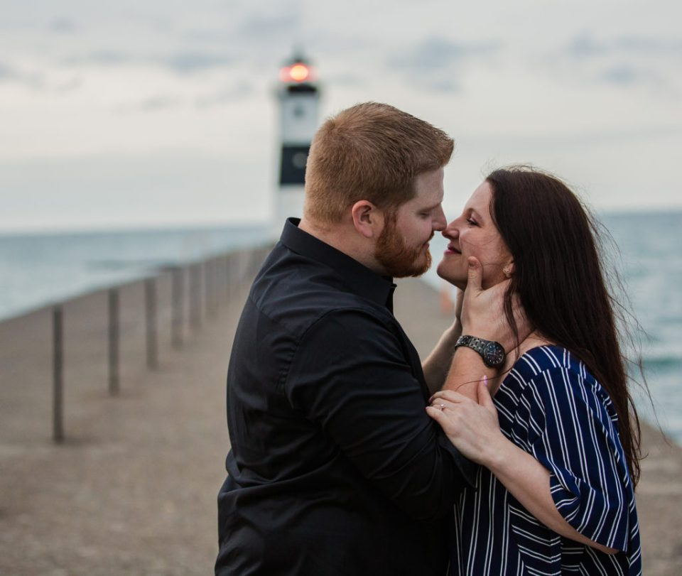 couple about to kiss in front of lighthouse on North Pier in Erie PA