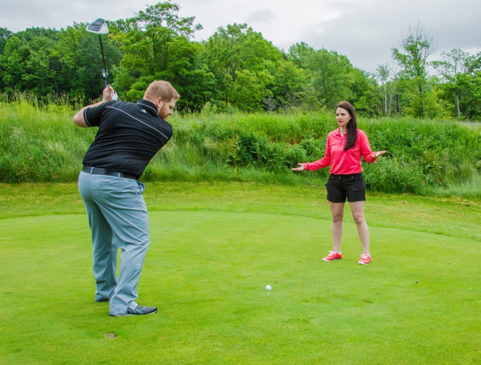 Woman watches as her fuance takes a shot on the Whispering Woods golf course in Erie, PA