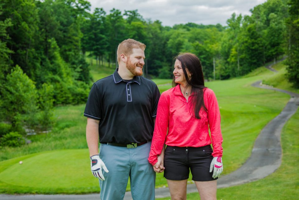 engaged couple hold hands at Whispering Woods golf course