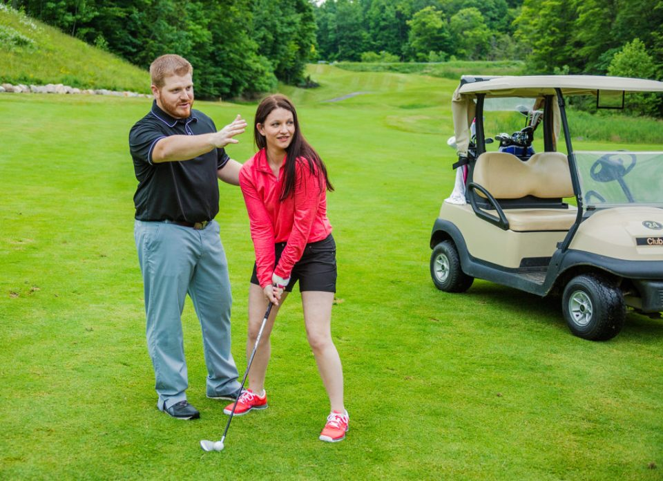 man shows fiancee how to golf at Whispering Woods golf course in Erie, PA