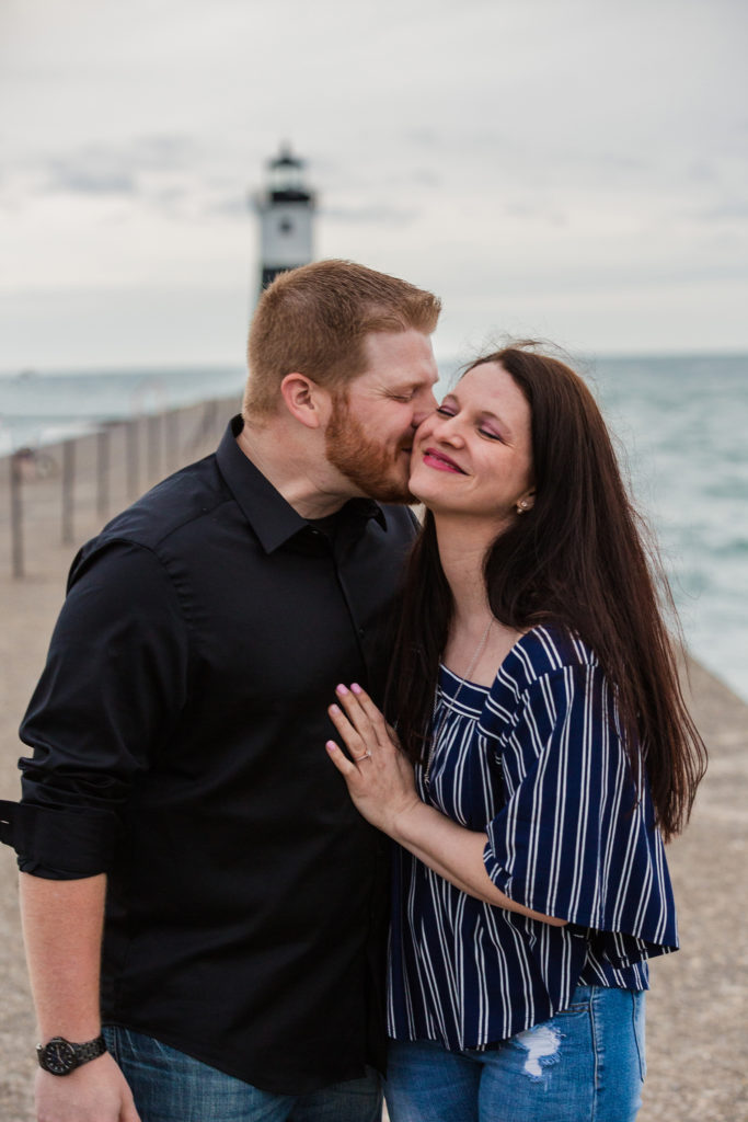 Man kisses fiancee on the cheek during engagement portraits at the North Pier in Erie PA