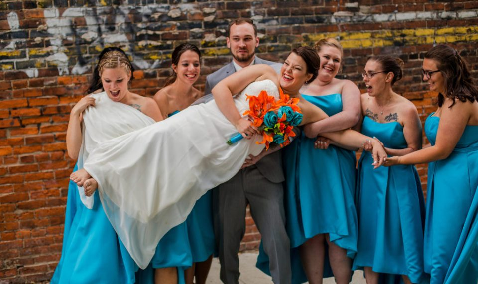 groom and bridesmaids hold up bride at Brewerie wedding in downtown Erie PA