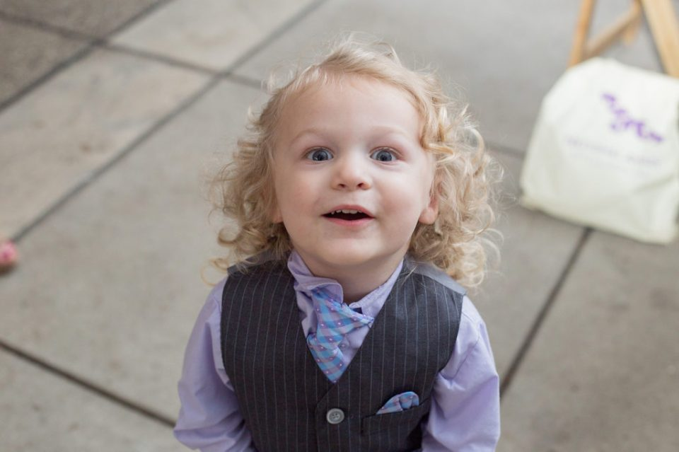 child smiling at camera during wedding reception in Erie PA
