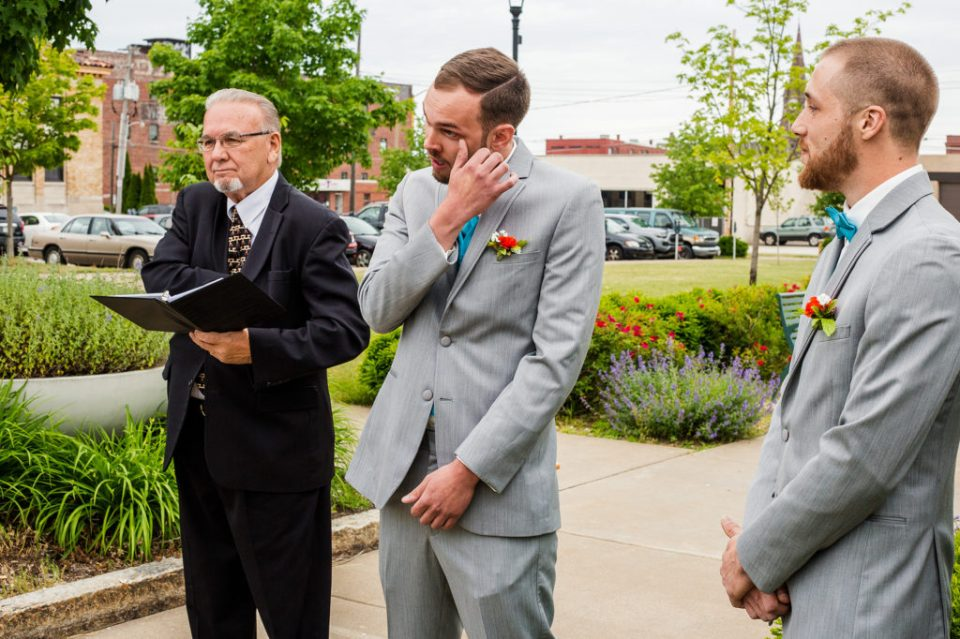 groom wipes away a tear at Erie PA wedding