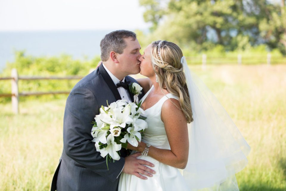 bride and groom kiss on the greens at Lawrence Park Golf Club