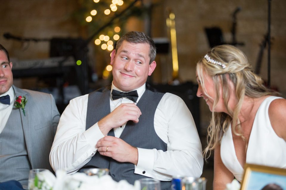 After, Saint Patrick's wedding, bride and groom share a laugh at their reception at the Masonic Temple in Erie PA