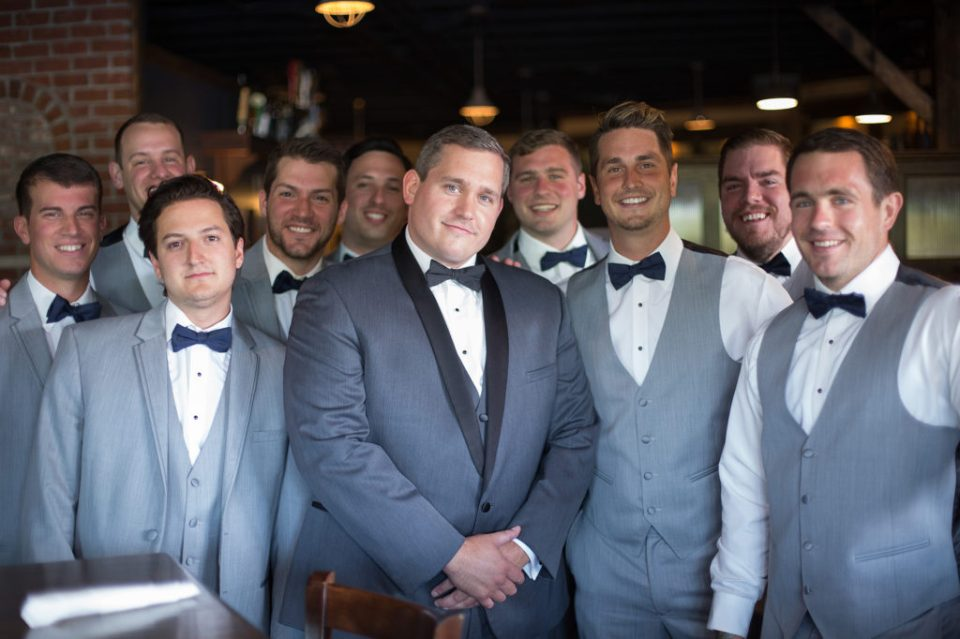 Erie PA groom and groomsmen pose for a photo at the Tap House in downtown Erie