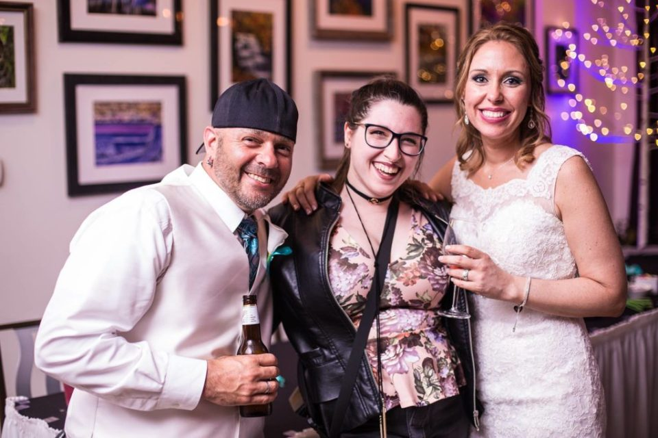 Erie PA second photographer, Kayla Amendola, poses with bride and groom at wedding reception