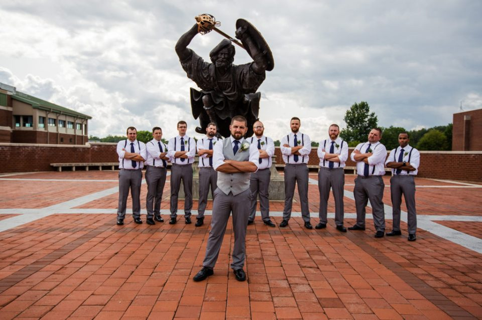 groom poses with groomsmen in front of Angus, the Fighting Scot, at Edinboro University wedding