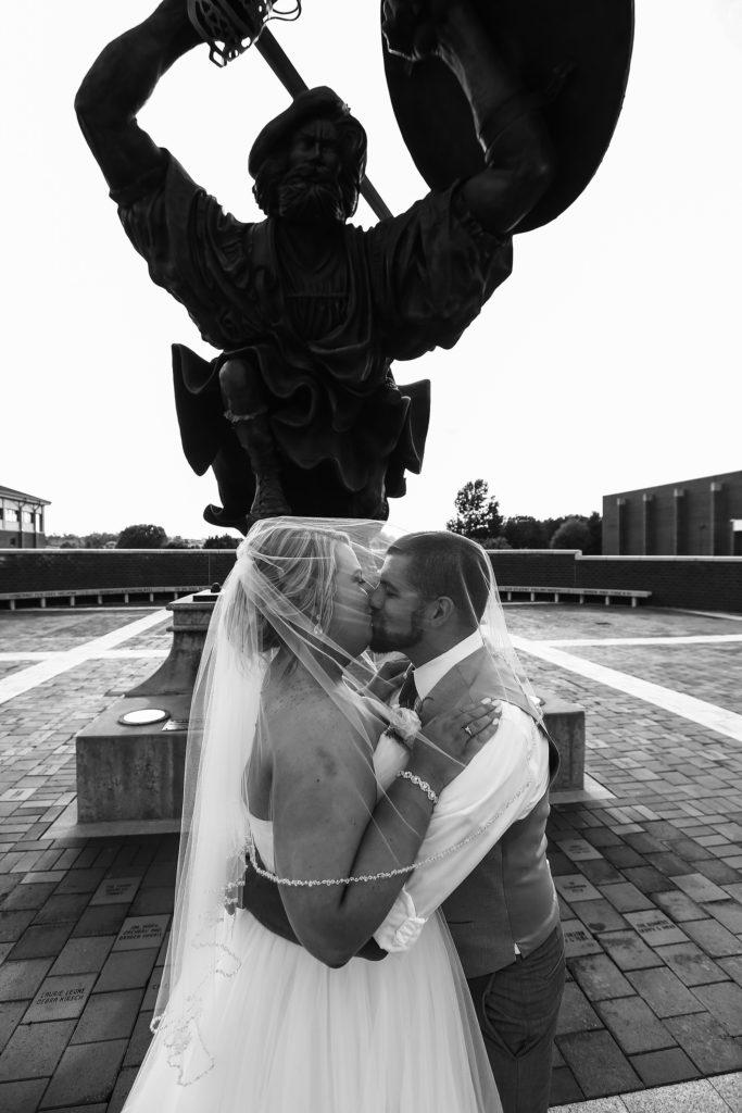 bride and groom kiss under the Fighting Scot statue at Edinboro University wedding