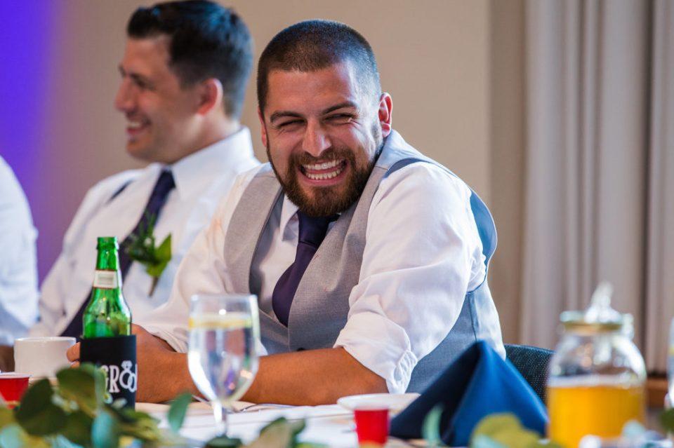 groom laughs during toasts at Edinboro University wedding