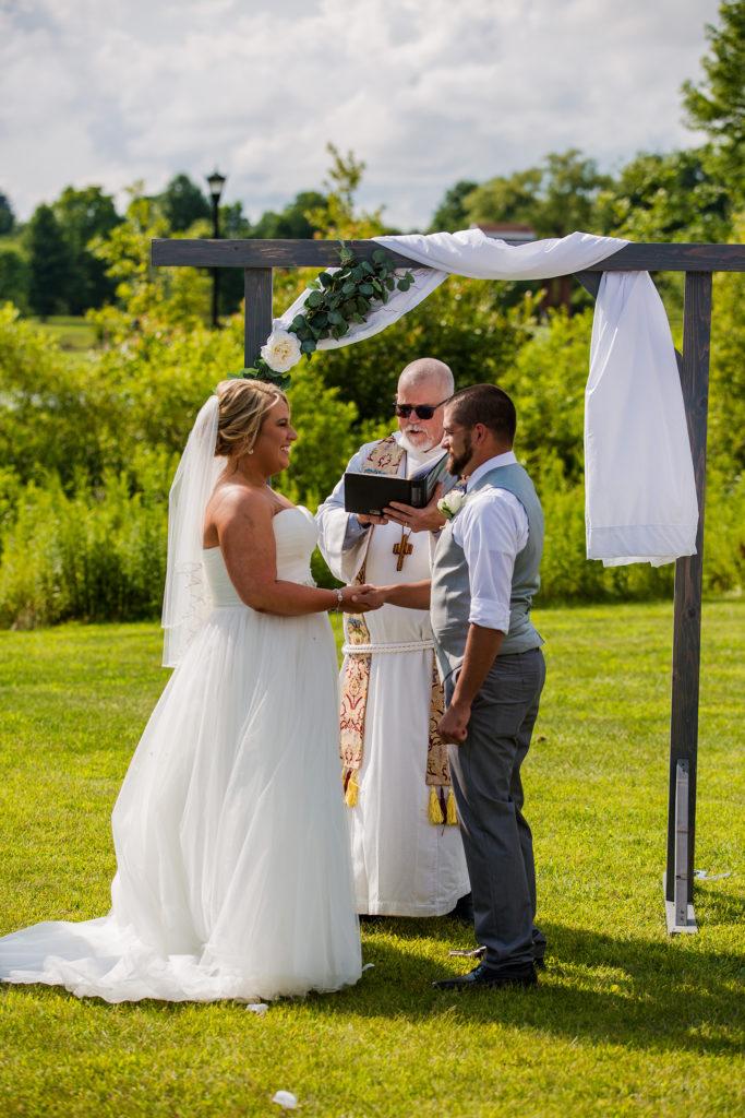bride and groom exchange vows under handmade arch at Edinboro University wedding