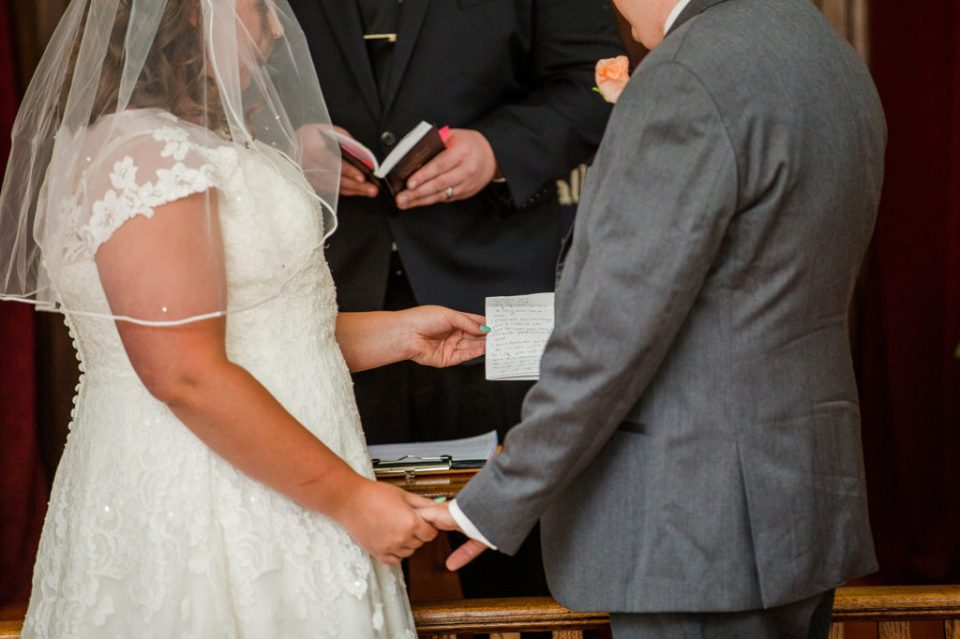 bride and groom exchanging rings at Torpedo Community Church