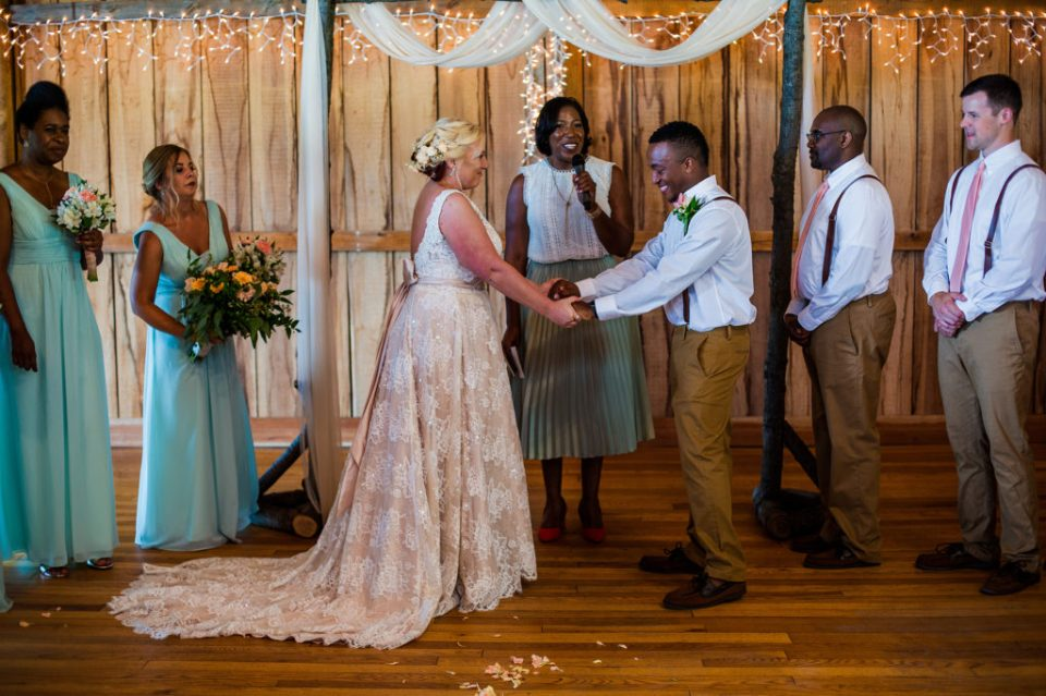 couple exchanges vows indoors at Betsy's Barn wedding