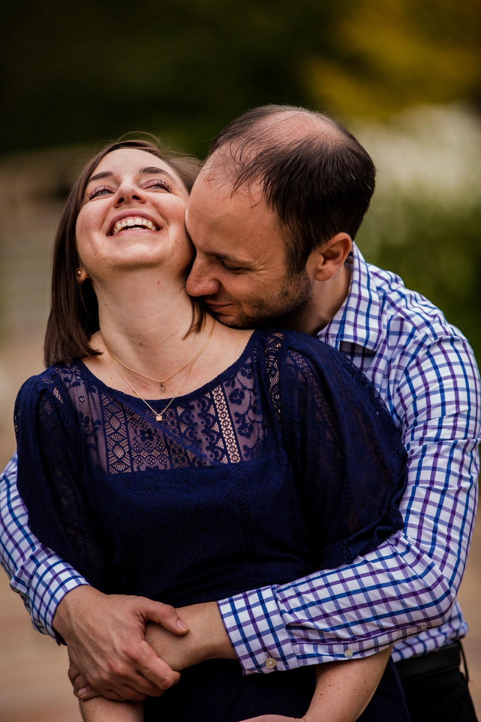 Pittsbugh PA Man hugs his fiancee from behind while she laughs on a walk in Mellon Park