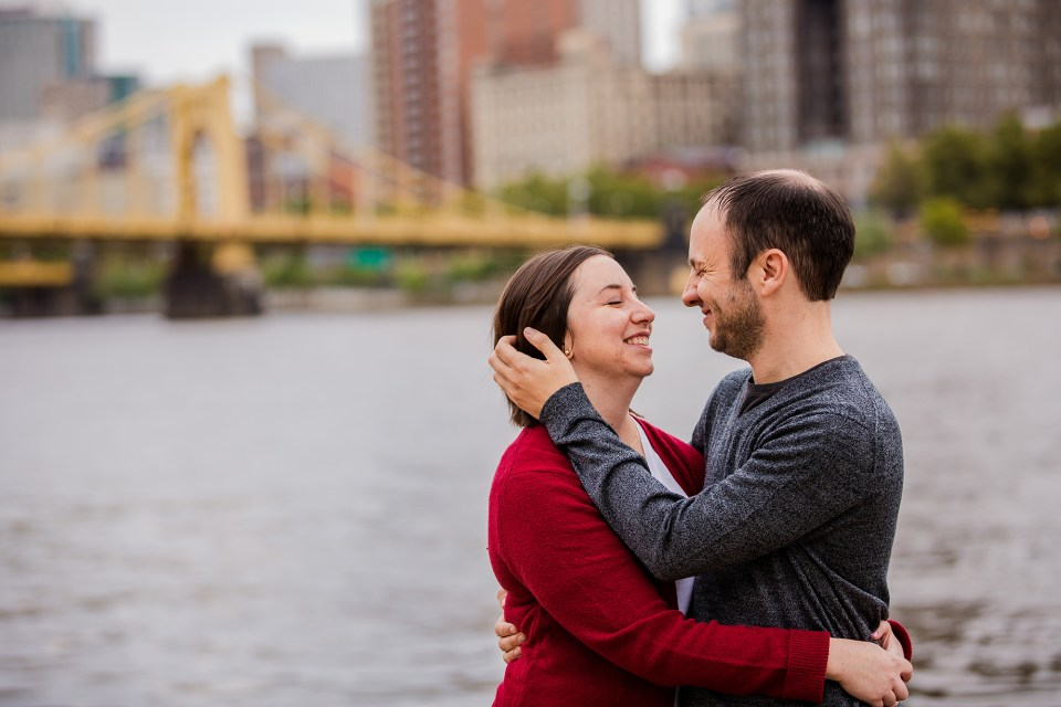 Couple poses for engagement photo along the river with Pittsburgh PA skyline in the background