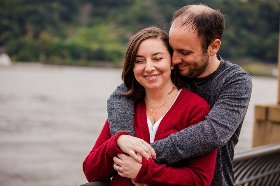 Engaged couple embrace along the river in Pittsburgh PA